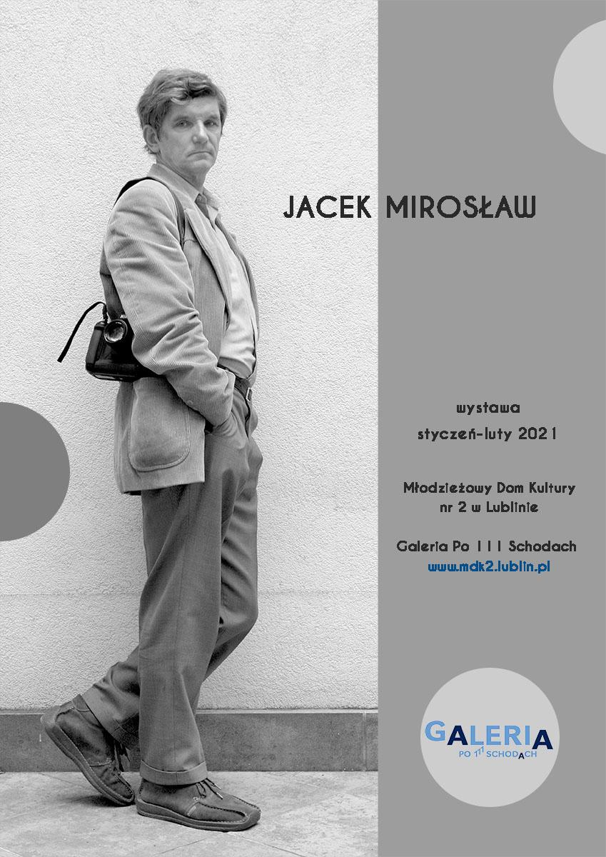 """plakat z wystawy Jacka Mirosława . Na szarym tle postać """"en pied"""" autora, który aparat ma przewieszony na ramieniu a jedną z dłoni schowaną w kieszeni spodni"""